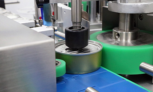 Cans being labeled by a labeling machine