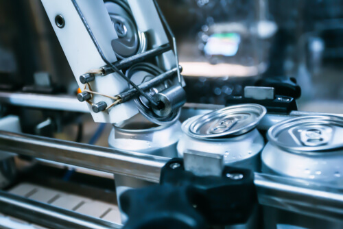 An automatic machine rolls up the lids on the beer cans