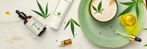 Cosmetics with cannabis oil on a turquoise plate on a light marble background_1498231697